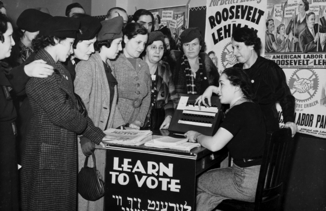 Women surrounded by posters in English and Yiddish supporting Franklin D. Roosevelt, Herbert H. Lehman, and the American Labor Party teach other women how to vote, 1935